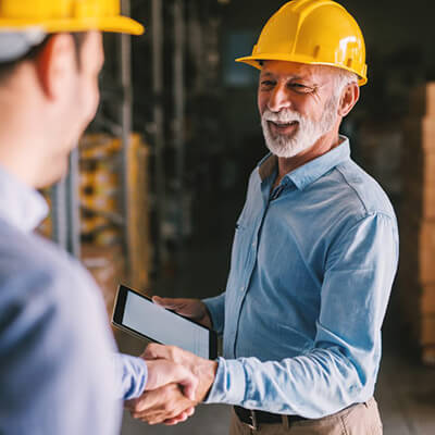 man in yellow hardhat shaking hands with another man in a hardhat