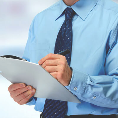 man in a blue dress shirt holding a clipboard and a pen