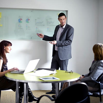 businessman presenting data to other businesspeople in a meeting room