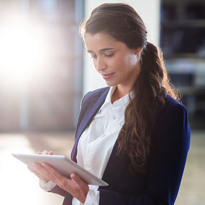 businesswoman looking down at a tablet